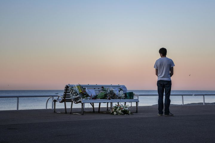 A man looks at a tribute laying on a bench near where a person was killed on the Promenade des Anglais on July 17, 2016.
