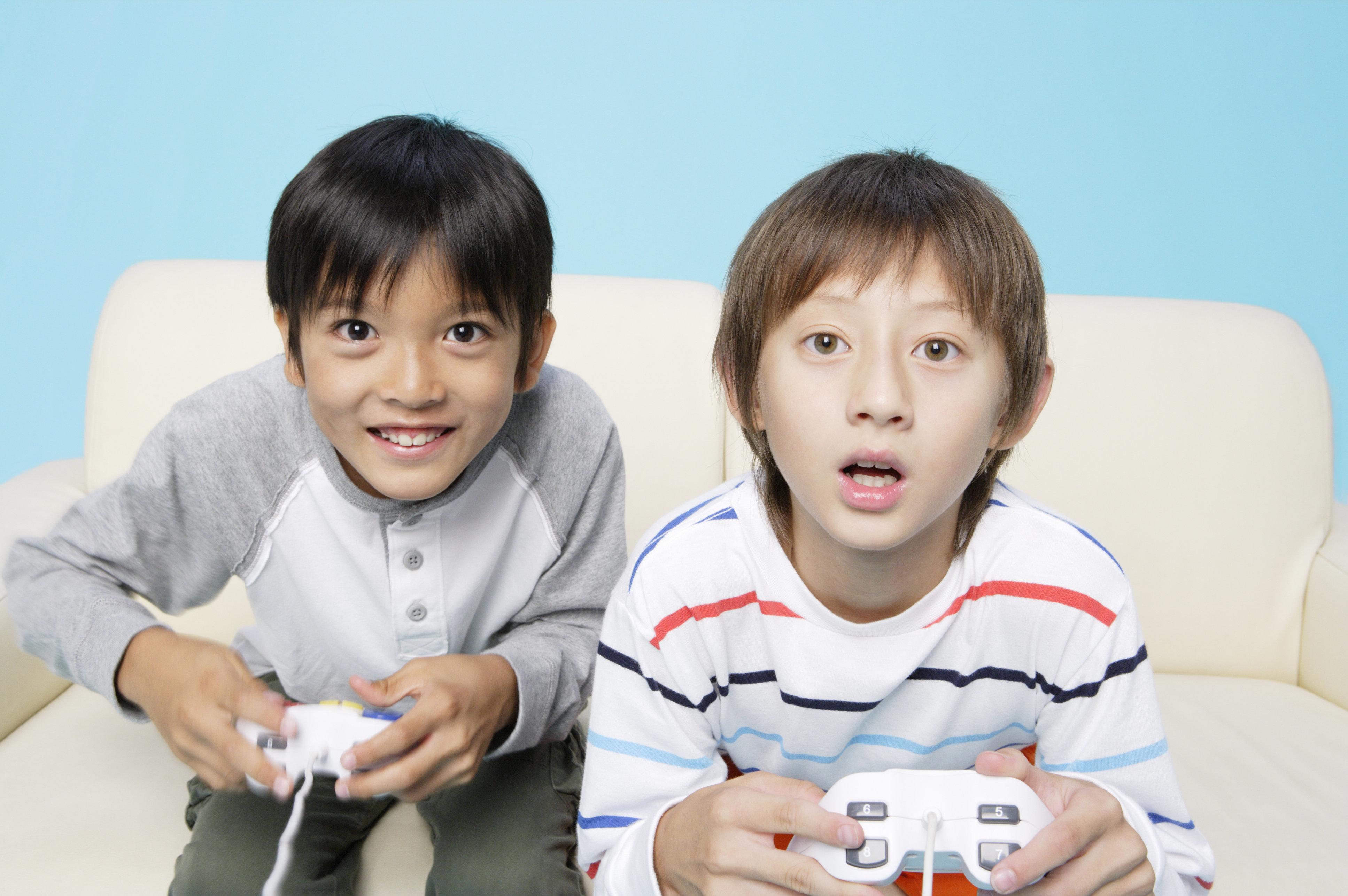 Boys playing video game, studio shot