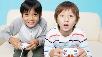 Boys playing video game, studio shot