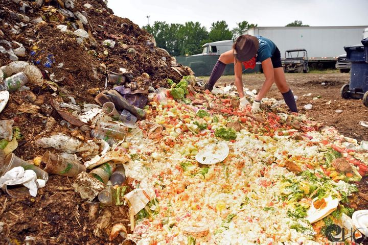 A Clean Vibes volunteer works to sort a compost pile at Bonnaroo Music Festival in Tennessee in June 2016.