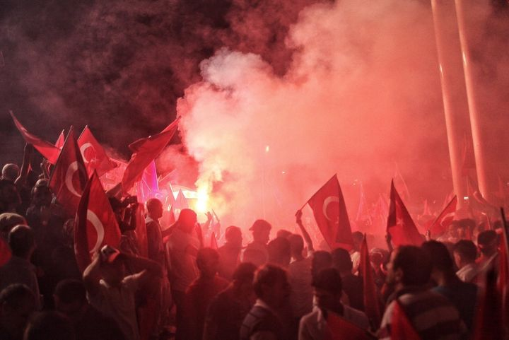 Supporters of Turkish President Tayyip Erdoğan light flares as they gather in Istanbul's central Taksim Square on July 18, 20