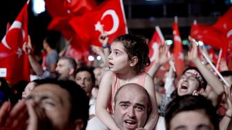 ISTANBUL, TURKEY - JULY 19: People listen to Turkey's Former Prime Minister Ahmet Davutoglu during a protest against Parallel State/Gulenist Terrorist Organization's failed military coup attempt at Taksim Square in Istanbul, Turkey on July 19, 2016.  (Photo by Abdullah Coskun/Anadolu Agency/Getty Images)