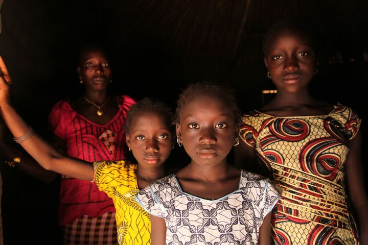 A woman and her daughters stand in their home, in the village of Cambadju, Guinea-Bissau. Their village is the first in the c