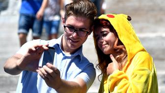 Gamers use the Pokemon Go application on their mobiles in central Rome on July 19, 2016. Since its launch two weeks ago, the game for mobile gadgets has sparked a worldwide frenzy among users who have taken to the streets with their smartphones. The free app uses satellite locations, graphics and camera capabilities to overlay cartoon monsters on real-world settings, challenging players to capture and train the creatures for battles.  / AFP / TIZIANA FABI        (Photo credit should read TIZIANA FABI/AFP/Getty Images)