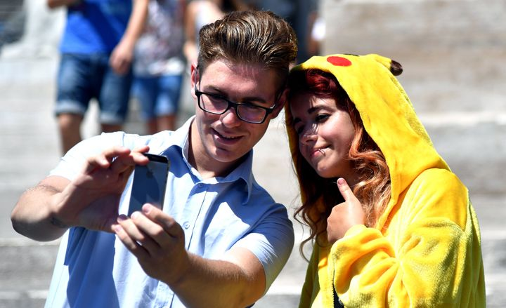 Gamers use the Pokemon Go application on their mobiles in central Rome on July 19, 2016.