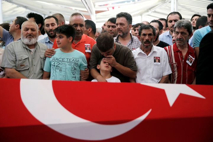 A man comforts the son of Erol Ince, a police officer who was killed during a thwarted coup, during a funeral ceremony at Ist