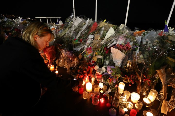 A woman lights a candle on July 18, 2016 in Nice, by the new makeshift memorial in tribute to the victims of the deadly Basti