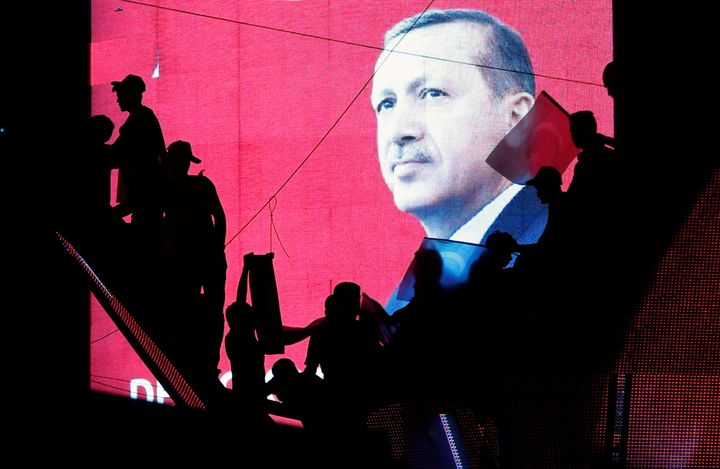 Turkish supporters are silhouetted against a screen showing President Recep Tayyip Erdogan during a pro-government