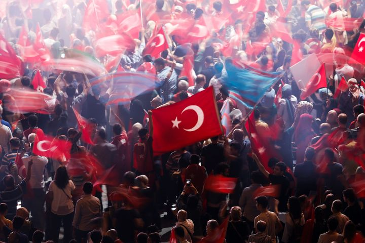 Supporters of Turkish President Recep Tayyip Erdogan wave Turkish national flags during a pro-government demonstration on Tak