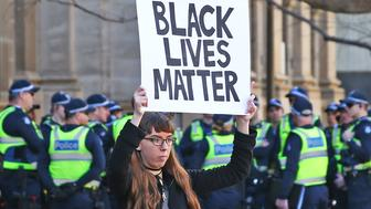 MELBOURNE, AUSTRALIA - JULY 17:  A woman holds a Black Lives Matter placard aloft as Australian police offcers look on during a rally to support the Black Lives Matter movement on July 17, 2016 in Melbourne, Australia. The rallies were organised in support of the Black Lives Matter following a spate of police shootings of African American people in the United States last week. The rallies are also aimed at highlighting Indigenous Australian deaths in custody.  (Photo by Scott Barbour/Getty Images)