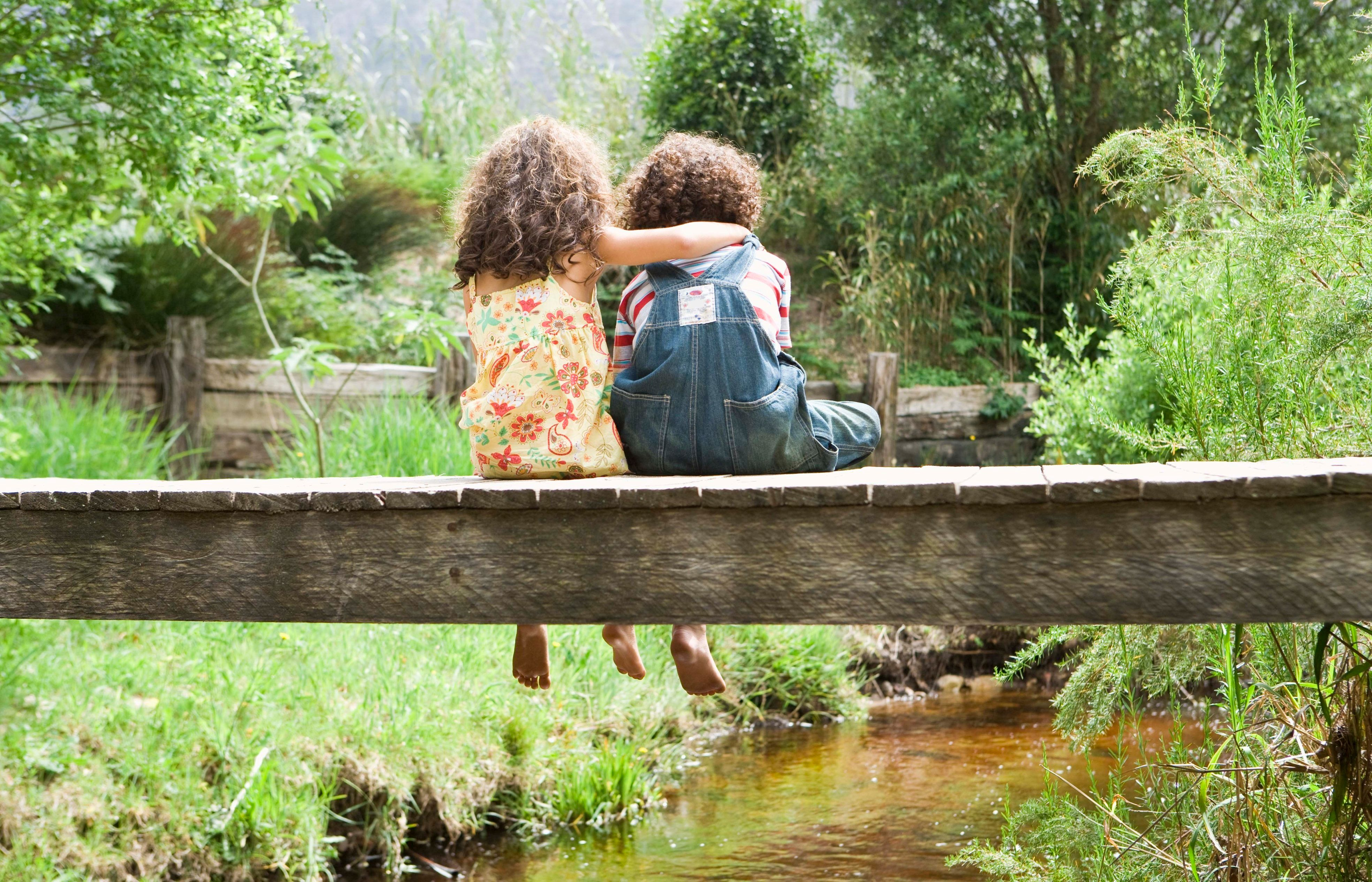 Girl embracing boy on footbridge over stream