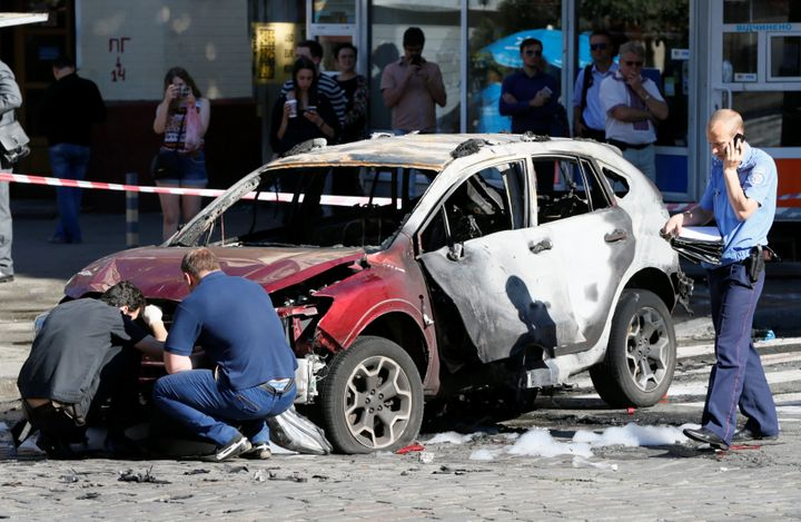 Investigators inspect a damaged car at the site where journalist Pavel Sheremet was killed by a car bomb in central Kiev, Ukr