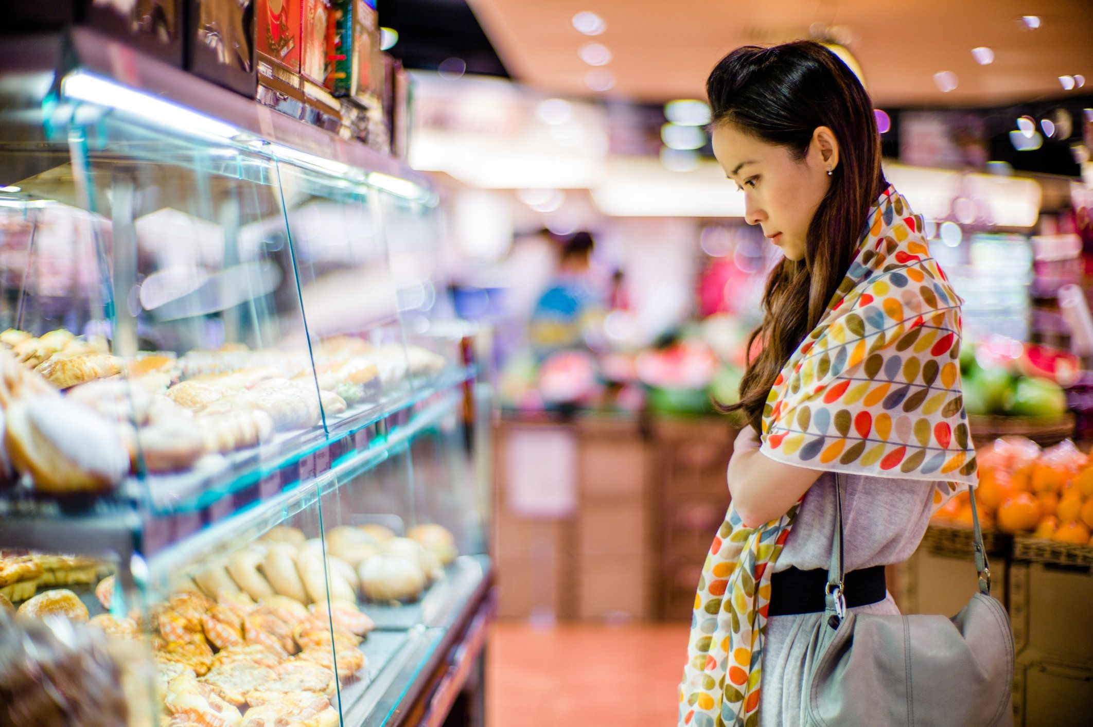 Pretty young lady looking at bakery display in a supermarket.