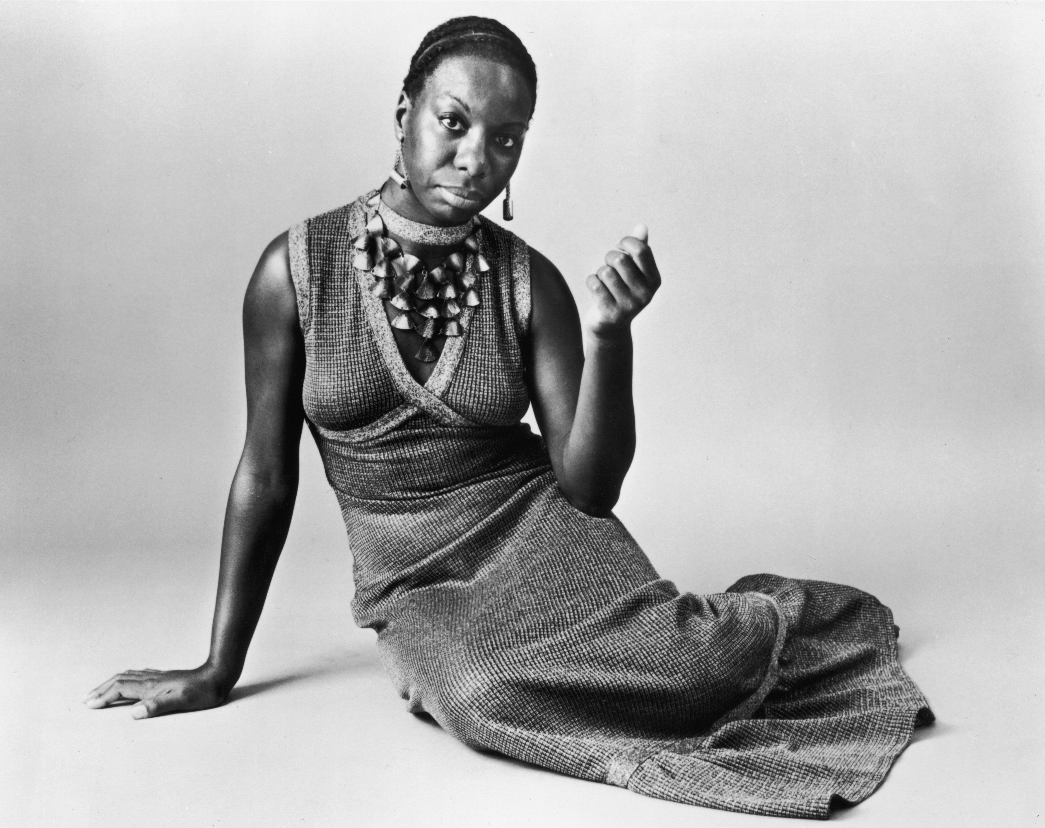 circa 1968:  Studio portrait of American pianist and jazz singer Nina Simone (1933 - 2003) reclining on the floor while wearing a sleeveless, V-neck dress with a shell neckpiece.  (Photo by Hulton Archive/Getty Images)