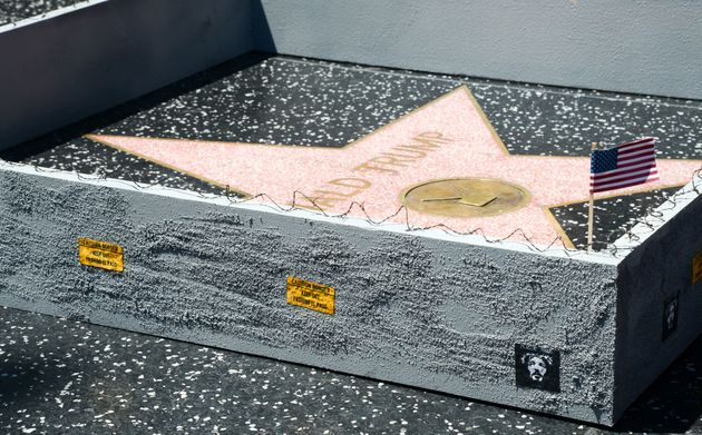 LA-based street artist Plastic Jesus erected a 6-inch concrete wall around Donald Trump's Hollywood Walk...