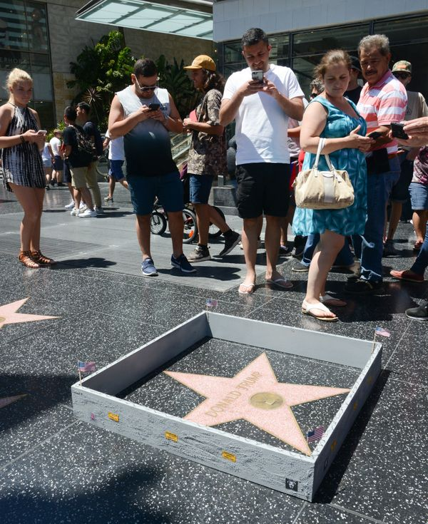 Onlookers in Hollywood take photos of a wall street artist Plastic Jesus built around Donald Trump's star on the Hollyw