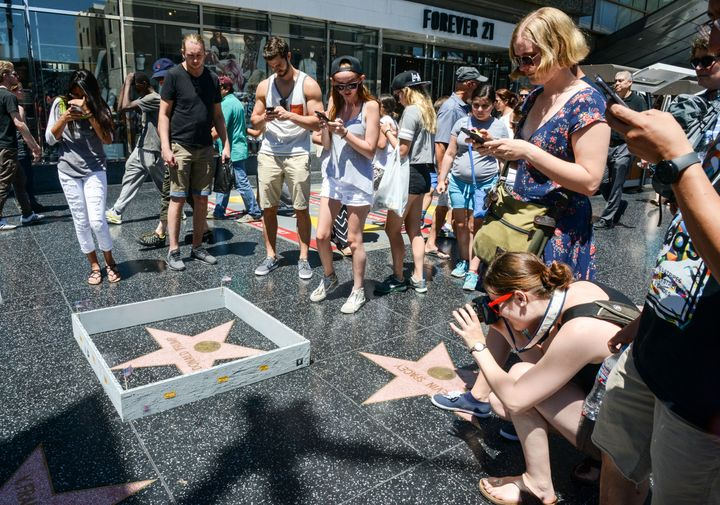 Onlookers take photos of the Plastic Jesus installation -- a miniature wall -- built around Donald Trump's Hollywood Walk of Fame star.