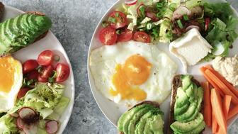 Fried egg with avocado toast and salad