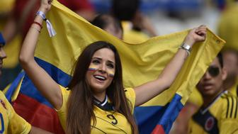 A Colombia fan holds her national flag before a Group C football match between Colombia and Greece at the Mineirao Arena in Belo Horizonte during the 2014 FIFA World Cup on June 14, 2014.  AFP PHOTO / ARIS MESSINIS        (Photo credit should read ARIS MESSINIS/AFP/Getty Images)