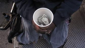 NEW YORK - OCTOBER 23:  A homeless man who goes by the name Cleveland displays a cup containing money from panhandling on October 23, 2009 in New York City. In a recently released report by the advocacy group Coalition for the Homeless it was revealed that the numbers of homeless people using New York City shelters each night has reached an all time high. Since Mayor Michael Bloomberg took office eight years ago there has been a 45 percent increase in shelter use with over 39,000 homeless people, including 10,000 homeless families, checking in to city shelters every evening. The group also said that 2009 has turned out to be 'the worst on record for New York City homelessness since the Great Depression.  (Photo by Spencer Platt/Getty Images)