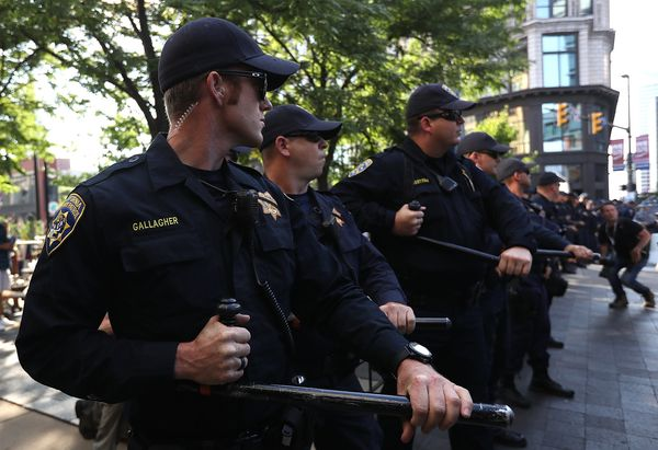California Highway Patrol officers hold their batons as they block the path of protesters.