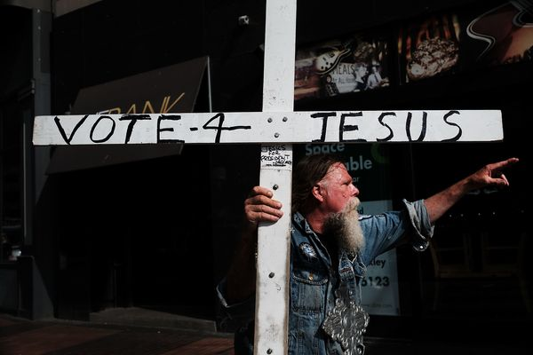 A man walks with a cross advocating voting for Jesus.
