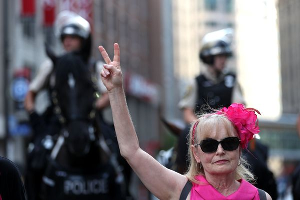 A member of the activist group Code Pink makes a peace sign while protesting.