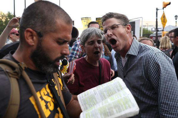 Protesters shout at a man reading Bible verses.