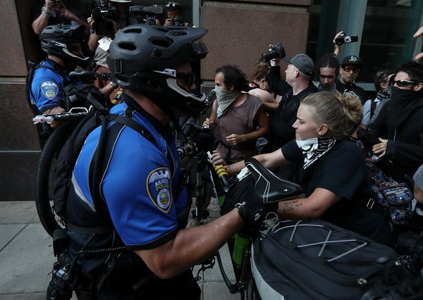 Police officers use bicycles to push back protesters.