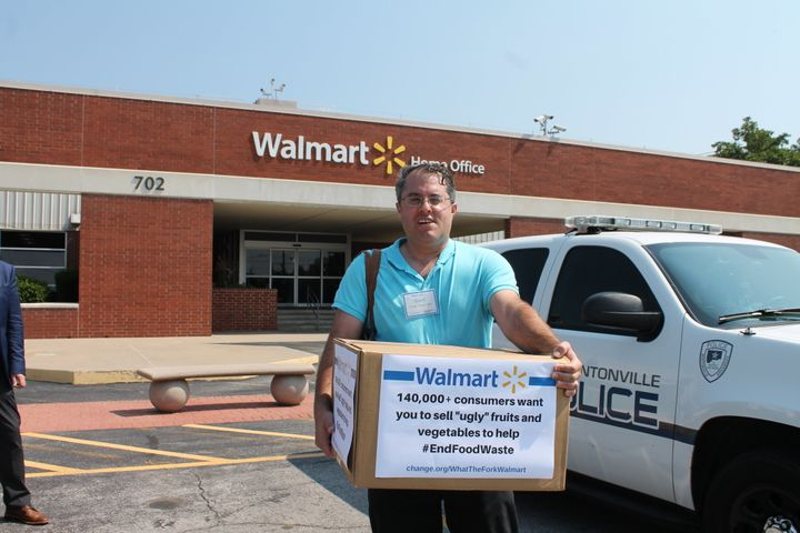 Food activist Jordan Figueiredo holds a box full of petition signatures of outside Walmart headquarters in Bentonville,
