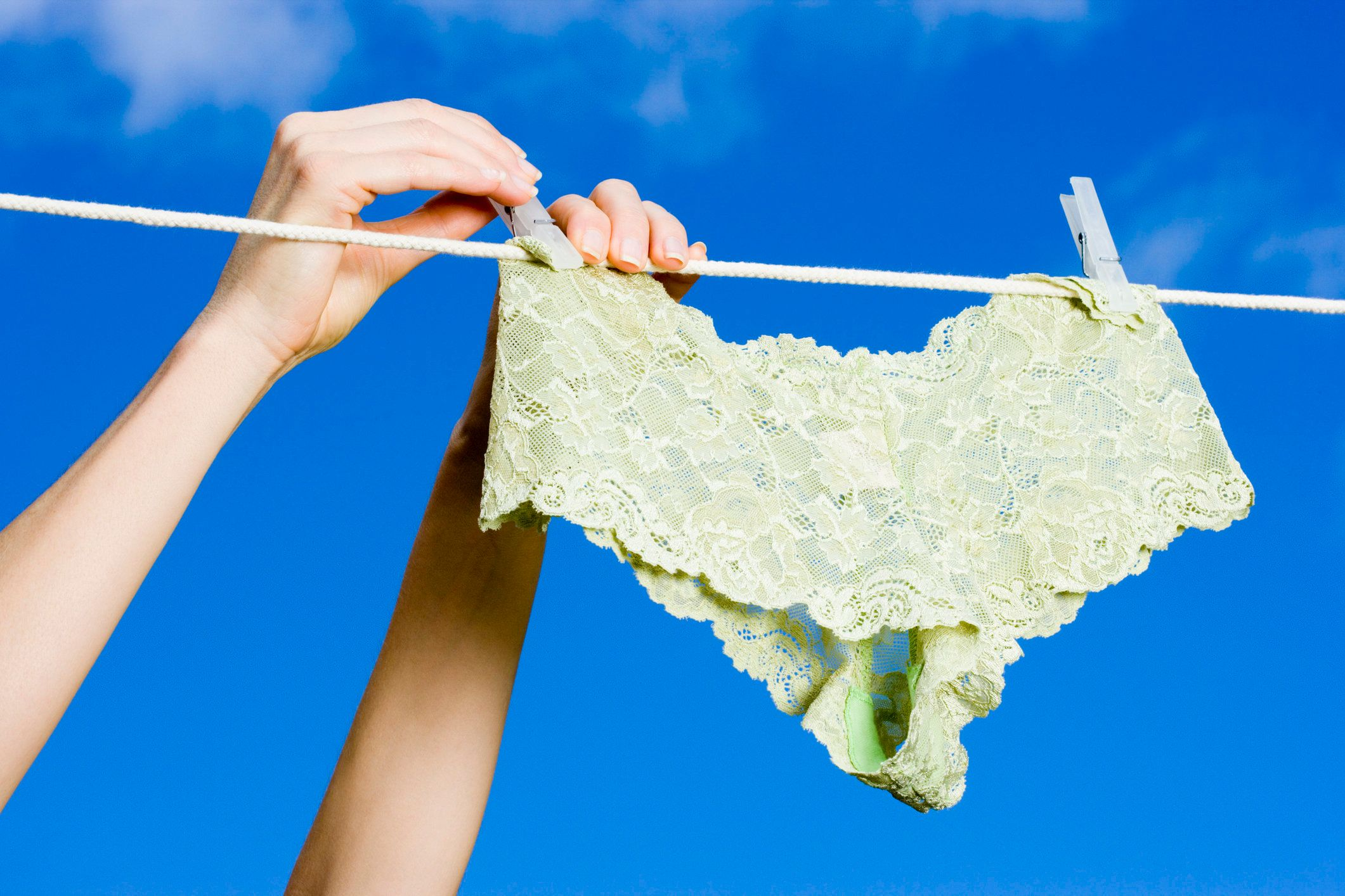 Hands hanging panties on clothesline
