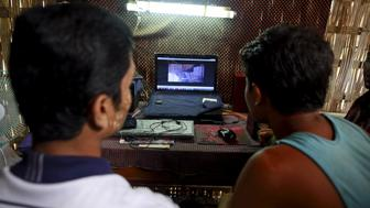 Rohingya Muslims watch Rohingya news at an Internet shop in a refugee camp outside Sittwe, Myanmar May 21, 2015. Picture taken May 21, 2015. REUTERS/Soe Zeya Tun