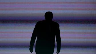 The silhouette of Donald Trump, presumptive 2016 Republican presidential nominee, is seen on stage during the Republican National Convention (RNC) in Cleveland, Ohio, U.S., on Monday, July 18, 2016. Republican factions trying to stop Donald Trump's nomination noisily disrupted a vote on party convention rules, displaying the fissures in the party on  the first day of its national convention. Photographer: David Paul Morris/Bloomberg via Getty Images