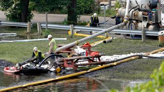 BATTLE CREEK, MI - JULY 28:  Workers try to clean up an oil spill of approximately 800,000 gallons of crude oil from the Kalamazoo River July 28, 2010 in Battle Creek, Michigan.  A 30 inch-wide underground pipeline owned by Calgary, Alberta-based Enbridge Energy Partners LP, began leaking on June 26.  (Photo by Bill Pugliano/Getty Images)