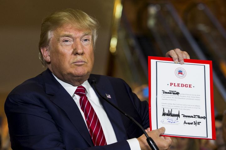 Trump shows off the pledge he signed at the request of Republican National Committee chairman Reince Priebus last year. Trump