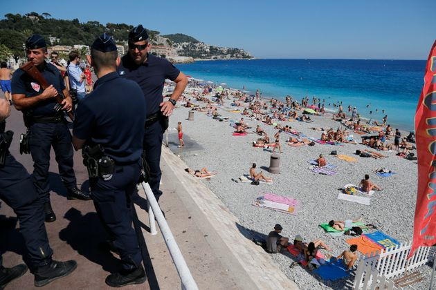 French CRS police patrol on the walkway above a public beach with sunbathers as security measures continue...