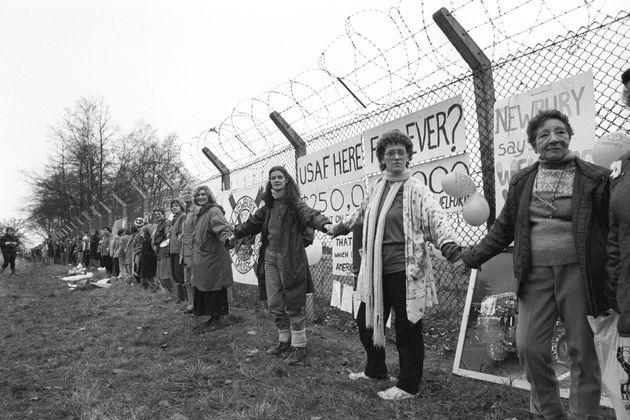 Women link hands at the Greenham Common Cruise Missile base during a demonstration marking the 6th anniversary...