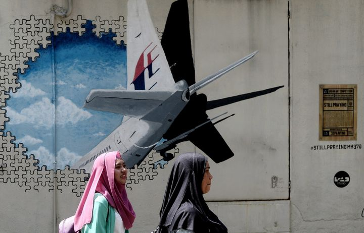 Malaysian women walk in front of a mural of missing Malaysia Airlines MH370 plane. The search, over 120,000 square kilom