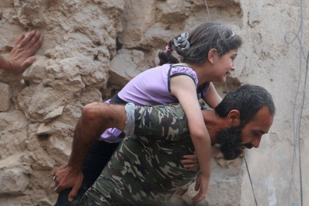A man carries an injured girl after an airstrike on Aleppo's rebel held Kadi Askar area, on 8
