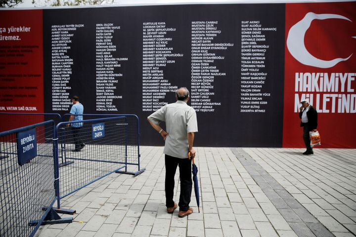 A man reads a banner with the names of civilians and policemen who were killed while resisting the coup attempt in Taksim squ