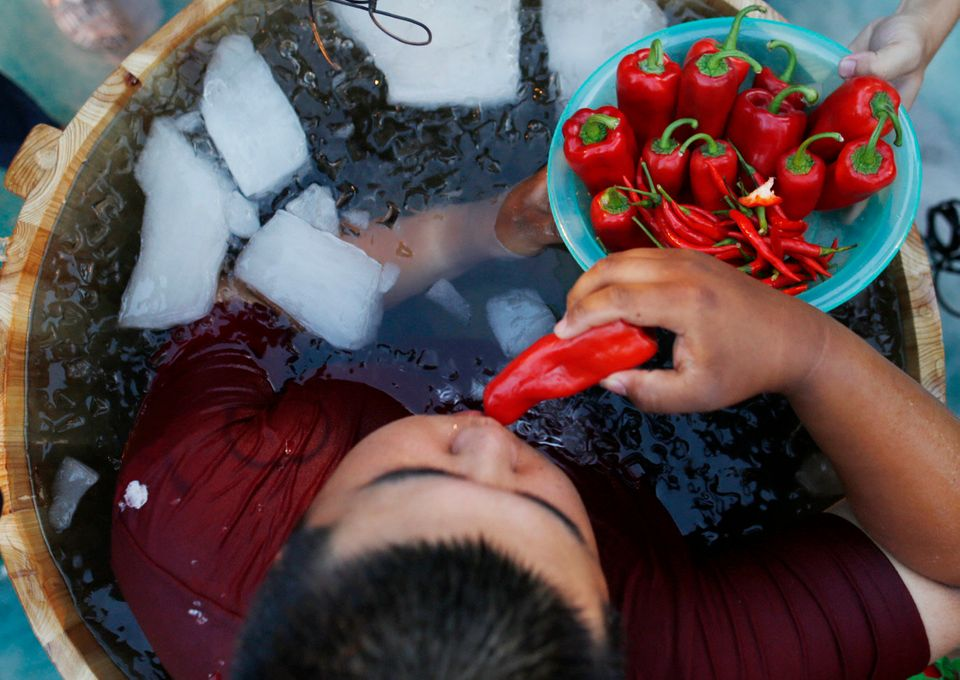 A man sitting in an ice bucket eats peppers during a competition at Song Dynasty Town on July 20, 2016 in Hangzhou, Zhejiang