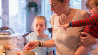 Caucasian mother and children cooking in kitchen