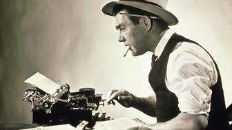 Side profile of a journalist typing on a typewriter