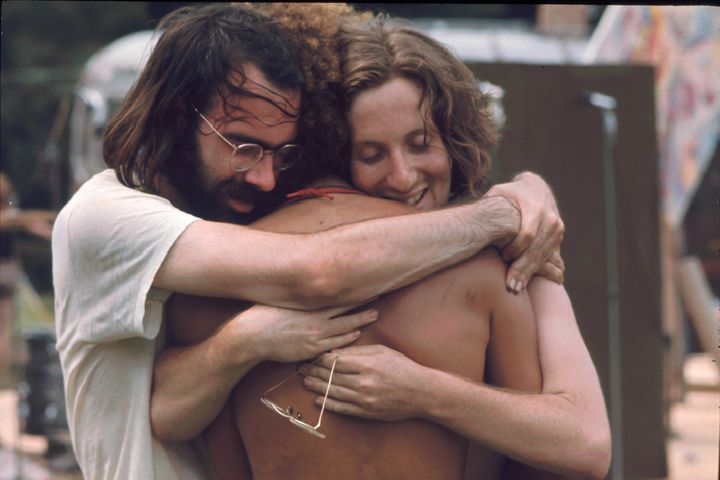 Three men attending the Woodstock music festival hug each other in August 1969. Woodstock co-founder Joel Rosenman