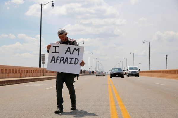A man crosses the Hope Memorial Bridge behind an anti-Trump protest to coincide with the Republican National Convention.