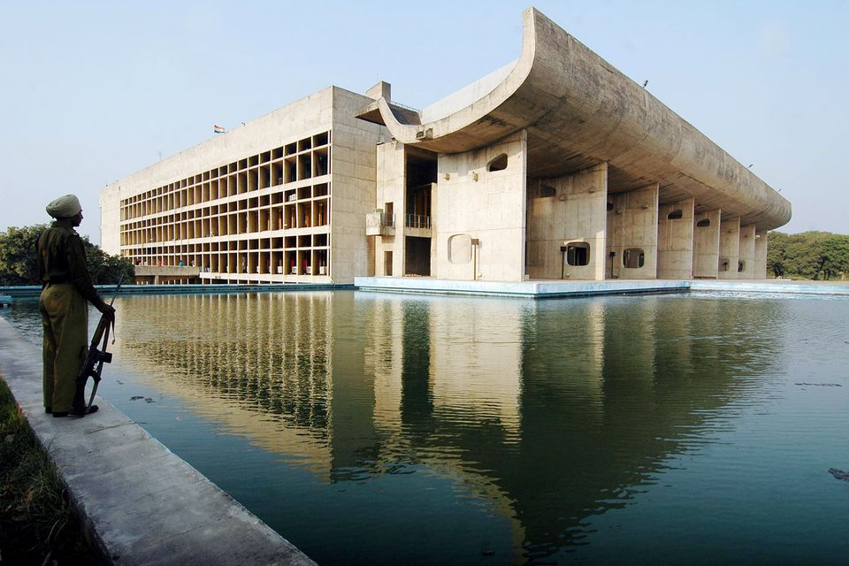 Aguard stands beside the Assembly Building in Chandigarh, the Indian city plannedby Le Corbusier...