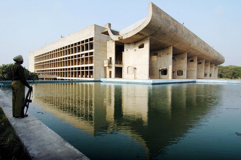 A guard stands beside the Assembly Building in Chandigarh, the Indian city planned by Le Corbusier in the 1950s.