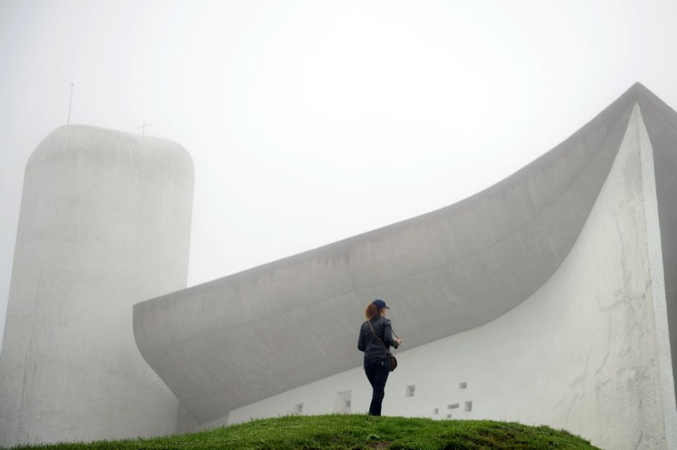 A visitor stands in front of Le Corbusier's Notre Dame du Haut chapel on Sept. 9, 2011, in Ronchamp, France. The chapel