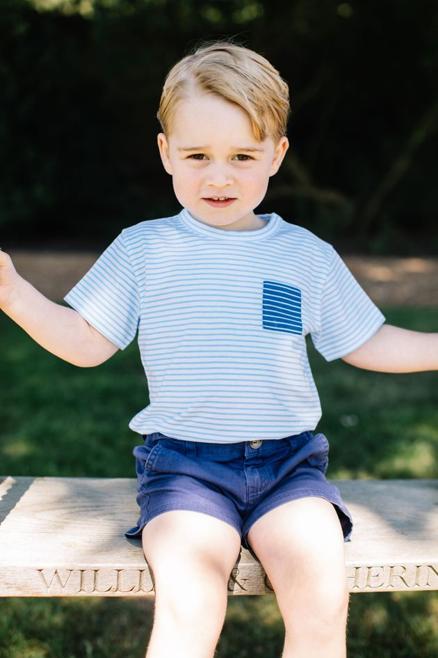 Prince George sits on a wooden swing, which is engraved with his parents' names, in one of the