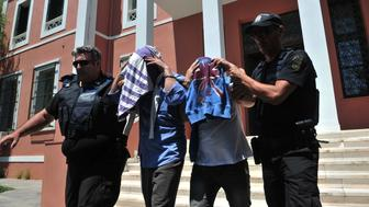 Turkish officers escorted by Greek police officers leave the courthouse of Alexandroupoli after appearing before a Greek prosecutor, on July 17, 2016.   Eight Turkish military personnel who fled to Greece by helicopter after July 15 failed coup took no part in the putsch, their lawyer said, although a Greek government spokeswoman contradicted their account. The eight, who have claimed asylum in Greece, arrived by military helicopter on July 16, 2016 after sending a distress signal to authorities at the airport in northern Alexandroupoli. / AFP / SAKIS MITROLIDIS        (Photo credit should read SAKIS MITROLIDIS/AFP/Getty Images)